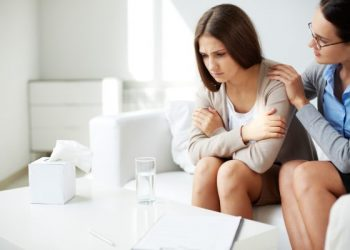 Image of young psychiatrist comforting her sad patient